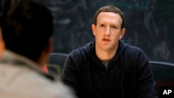 FILE - Facebook CEO Mark Zuckerberg meets with entrepreneurs and innovators during a round-table discussion in St. Louis, Nov. 9, 2017. Facebook announced an effort to remove false information that could lead to violence.