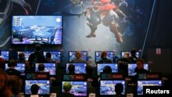 """Visitors play the """"Final Fantasy XIV: A Realm Reborn"""" video game at an exhibition stand during the Gamescom 2014 fair in Cologne August 13, 2014."""
