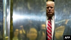 FILE - Donald Trump boards the elevator at Trump Tower in New York City, Jan. 16, 2017.