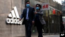 រូបឯកសារ៖ អតិថិជនដើរកាត់ស្លាកសញ្ញាក្រុមហ៊ុន Adidas និងក្រុមហ៊ុន H&M នៅក្នុងមជ្ឈមណ្ឌលពាណិជ្ជកម្មមួយក្នុងទីក្រុងប៉េកាំង ប្រទេសចិន ថ្ងៃទី២៥ ខែមីនា ឆ្នាំ២០២១។