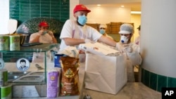 Pizzas are being prepared for home delivery at the Caputo pizzeria in Naples, Monday, April 27, 2020. Region Campania allowed cafes and pizzerias to reopen for delivery Monday, after a long precautionary closure due to the coronavirus outbreak. (AP Photo/Andrew Medichini)