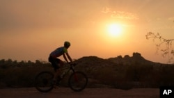 A cyclist bikes past the setting sun at Papago Park during a heatwave where temperatures hit 46 degrees Celsius Tuesday, June 15, 2021, in Phoenix. (AP Photo/Ross D. Franklin)