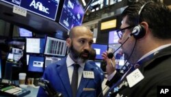 FILE - Specialist Fabian Caceres (L) and trader Michael Capolino confer on the floor of the New York Stock Exchange, Aug. 14, 2018.