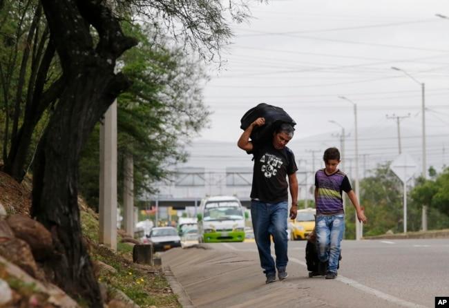 En esta foto del 28 de junio de 2018, el padre venezolano Darwin Zapata camina con su hijo de 12 años por una carretera en Cúcuta, Colombia, mientras se dirigen a Perú.