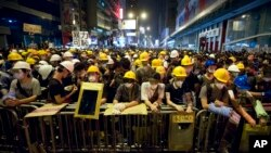 10月20日凌晨抗議示威人士在旺角街頭的鐵欄後守護佔領區。