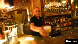 A waiter serves a drink at Cafe Savoy, which is a lesbian, a gay, bisexual and transgender (LGBT) cafe, in Vienna, Austria, Mar. 20, 2013.