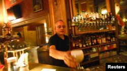 Seorang pramusaji menghidangkan minuman di sebuah kafe di Wina, Austria. (Foto: Ilustrasi)