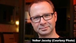 Voker Jakobi (Volker Jacoby) Yevropada Xavfsizlik va Hamkorlik Tashkiloti, shuningdek, BMTda ishlagan. Bugungi kunda Vashingtondan turib tahlilchilik qiladi.