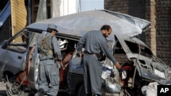 Afghan police officials investigate a damaged vehicle at the site of an explosion in Jalalabad, Nangarhar province east of Kabul, Afghanistan. At least three policemen were killed and six others injured in a bomb explosion, police officials said, April 21