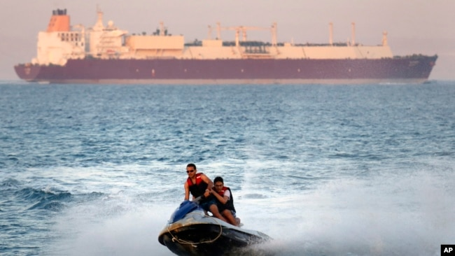 In this Friday, July 26, 2019 file photo, a ship crosses the Gulf of Suez towards the Red Sea as holiday-makers ride a jet ski at al Sokhna beach in Suez, 127 kilometers (79 miles) east of Cairo, Egypt. (AP Photo/Amr Nabil)