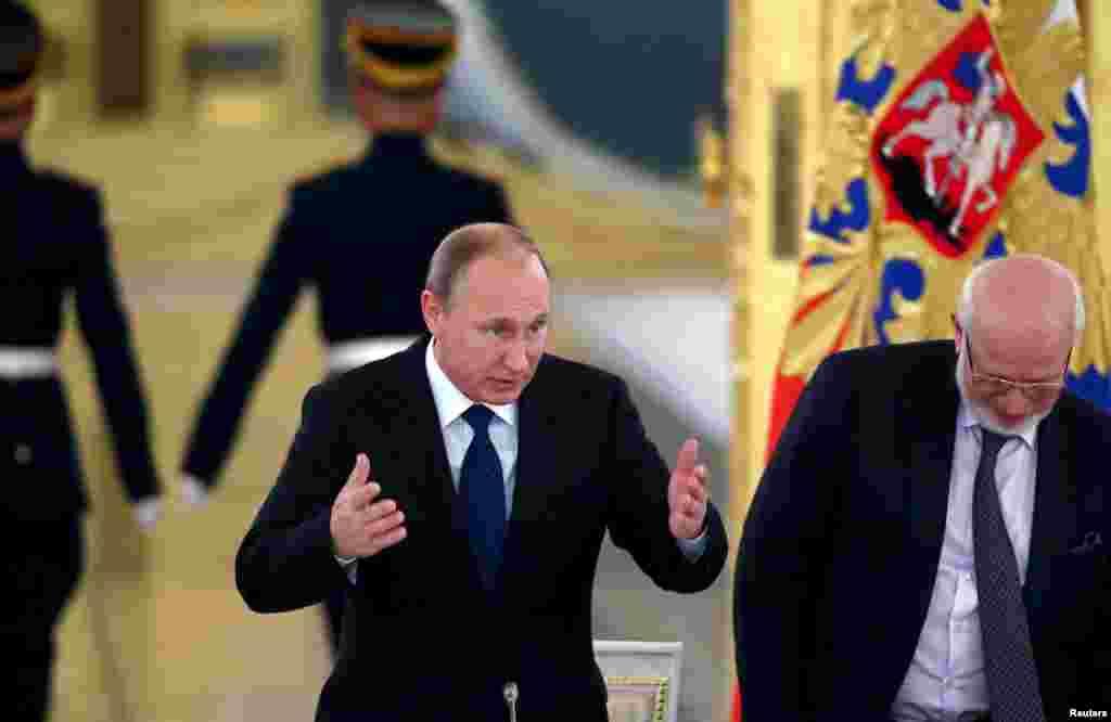 """Presiden Rusia Vladimir Putin menyapa para anggota Dewan Kepresidenan untuk Masyarakat Madani dan Hak Asasi Manusia di Kremlin. Putin mengatakan hari Kamis (1/10) bahwa kabar mengenai warga sipil yang tewas dalam serangan udara di Suriah adalah """"serangan informasi."""" (Reuters/Yuri Kochetkov/Pool)"""