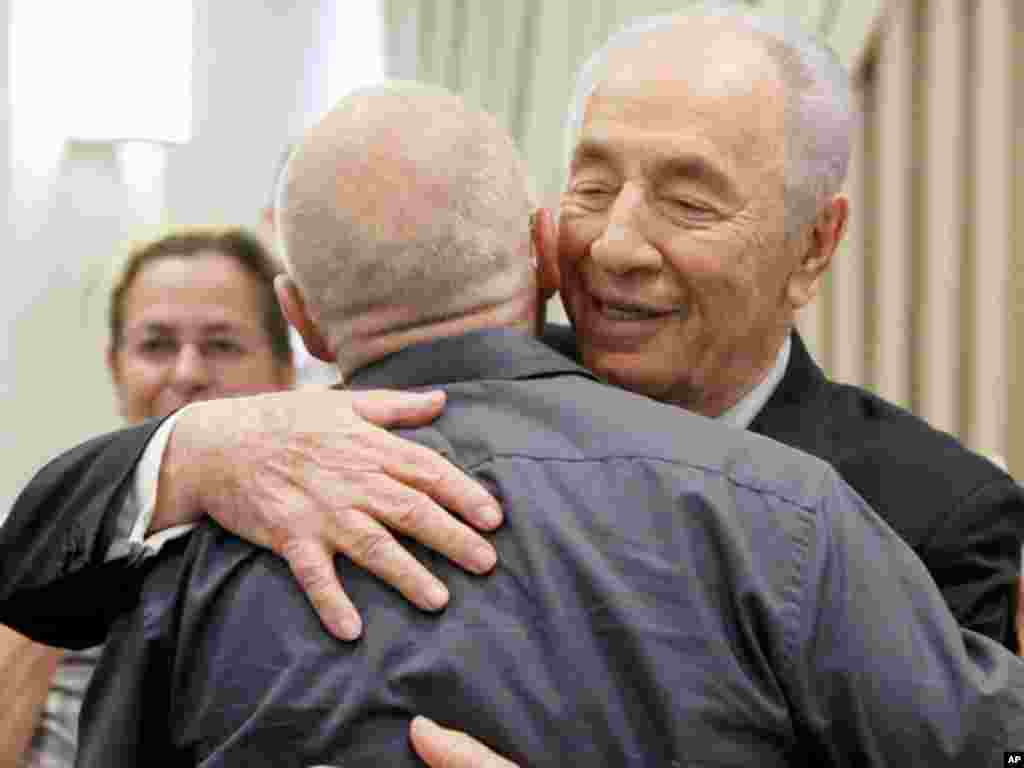 Israeli President Shimon Peres hugs Noam Shalit, father of captured Israeli soldier Gilad Schalit, at the president's residence in Jerusalem, October 12, 2011. Israel and Gaza's Hamas Islamist rulers agreed on Tuesday to swap more than 1,000 Palestinian p