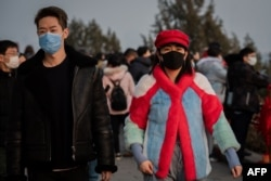 A couple wears masks to help stop the spread of a deadly virus as they walk at Jingshawn park, in Beijing, Jan. 25, 2020. China said it would close a section of the Great Wall and other famous Beijing landmarks to control the spread of the virus.