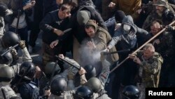 Radical protesters, including supporters of the All-Ukrainian Union Svoboda (Freedom) Party, clash with law enforcement members during a rally near the parliament building in Kyiv, Oct. 14, 2014.