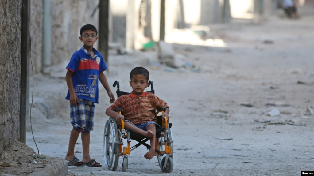 FILE - Boys, one of them in a wheelchair, venture down a street in the al-Sheikh Said neighborhood of Aleppo, Syria, Sept. 1, 2016.