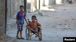 Halep'in Şeyh Said mahallesinde tekerlekli sandalyeli bir çocuk ve onu gezdiren arkadaşı (1 Mart 2016 - Abdalrhman Ismail - REUTERS)