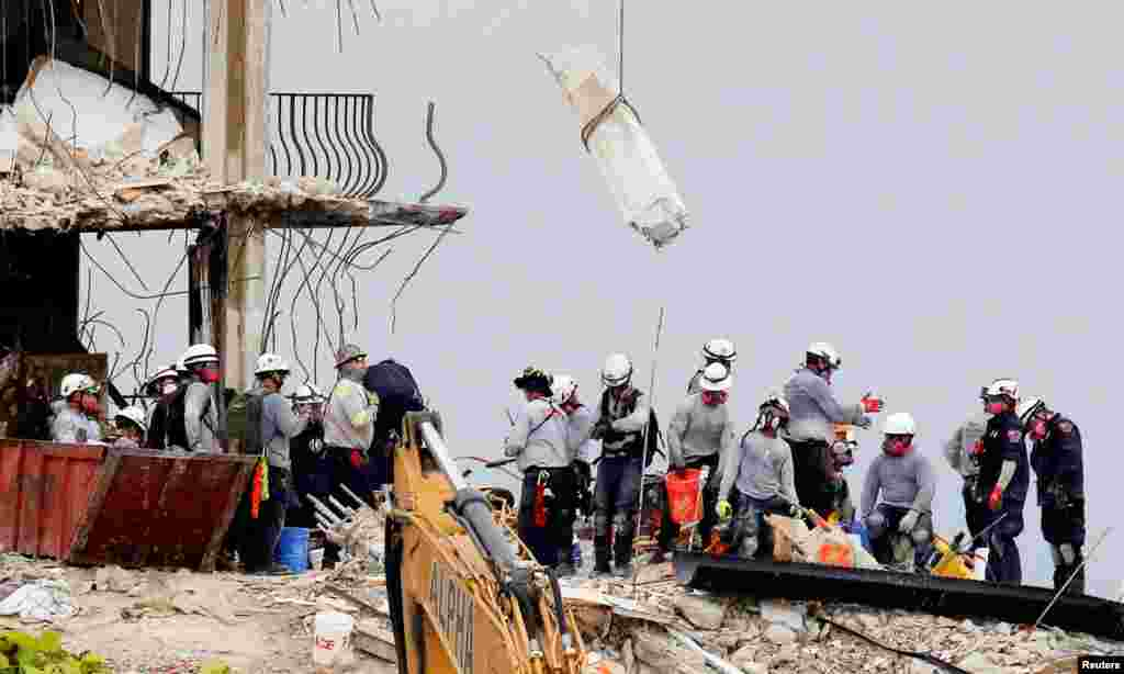 Emergency workers conduct search and rescue efforts at the site of a partially collapsed residential building in Surfside, near Miami Beach, Florida, June 30, 2021.