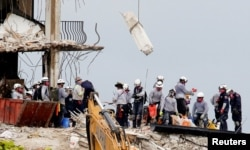 Emergency workers conduct search and rescue efforts at the site of a partially collapsed residential building in Surfside, near Miami Beach, Florida, U.S., June 30, 2021.