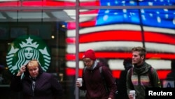 A woman pulls a hood over her head as she walks out of a Starbucks store into the cold wind at Times Square in New York, March 25, 2013.
