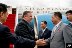 U.S. Secretary of State Mike Pompeo, second from left, is greeted by North Korean Director of the United Front Department Kim Yong Chol, center, and North Korean Foreign Minister Ri Yong Ho, second from right, as he arrives at Sunan International Airport.