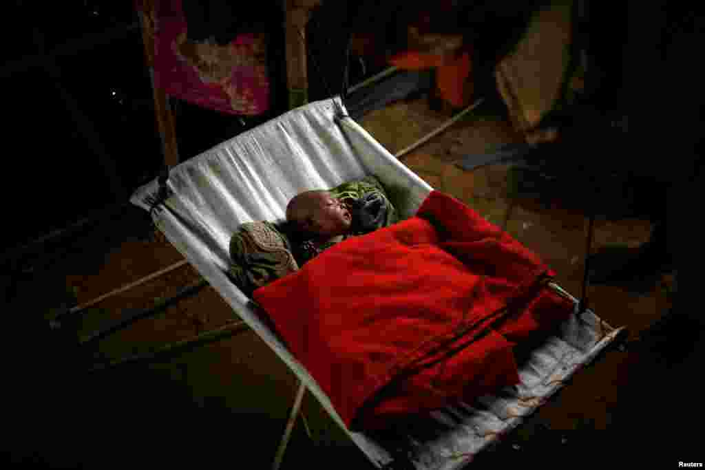 A Rohingya refugee baby girl sleeps inside her family's temporary shelter at the Balukhali refugee camp near Cox's Bazar, Bangladesh.