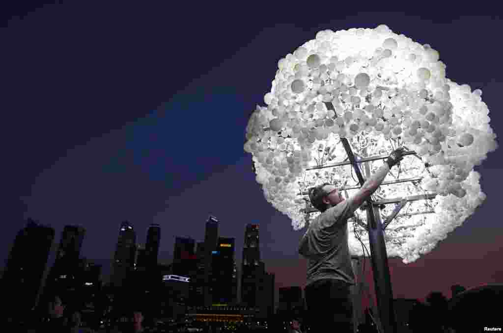 """Wayne Garrett of Canada makes final touches to his art installation """"Cloud"""" ,made up of 5000 new and recycled lightbulbs, along the Marina Bay in Singapore."""