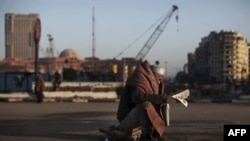 Египетский демонстрант читает газету после ночи, проведенной на площади Тахрир. 8 февраля 2011г.