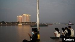 FILE - People uses their mobile phones on the Tonle Sap riverside in Phnom Penh, Cambodia, Feb. 18, 2021.