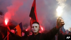Members of the nationalist movements light flares during a rally marking Defense of the Homeland Day in center Kyiv, Ukraine, Oct. 14, 2019.