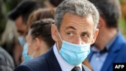FILE - Former French president Nicolas Sarkozy, wearing a face mask, attends a ceremony in Nice, Nov. 7, 2020.