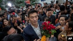 Thanathorn Juangroongruangkit, center, leader of the Future Forward Party is surrounded by his supporters as he arrives at Constitutional Court in Bangkok, Thailand, Nov. 20, 2019.
