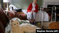 "Mary Derr, 93, sits on her bed and talks to her robot cat she calls ""Buddy"" in her home she shares with her daughter Jeanne Elliott in South Kingstown, Rhode Island."