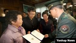 지난달 경북 청도군 청도읍에서 6·25전쟁 당시 전사한 김영탁 하사의 유가족들이 유해발굴감식단으로부터 김 하사의 신원 확인 통지서를 받고 있다. (자료사진)