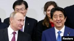 ປະທານາທິບໍດີຣັດເຊຍ ທ່ານ Vladimir Putin (ຊ້າຍ) ແລະນາຍົກລັດຖະມົນຕີຍີ່ປຸ່ນ ທ່ານ Shinzo Abe ຢູ່ກອງປະຊຸມ ຍີ່ປຸ່ນ-ຣັດເຊຍ ທີ່ນະຄອນໂຕກຽວ.