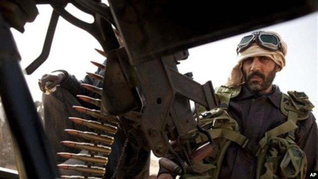 Libyan rebels who are part of the forces against Libyan leader Moammar Gadhafi sits on a truck with a heavy machine gun after capturing the oil town of Ras Lanuf, in eastern Libya, March 5, 2011