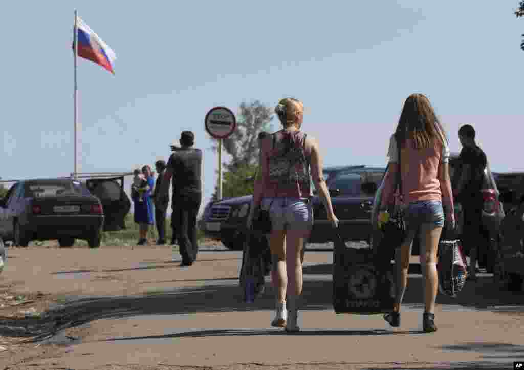 People carry their belongings as they walk to cross the border into Russia at the Ukrainian-Russian border checkpoint in Severniy, Luhansk region, eastern Ukraine, July 2, 2014.