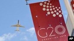 A jetliner flies over the G-20 summit venue at the Costa Salguero Center in Buenos Aires, Argentina, Nov. 28, 2018.