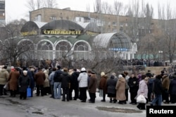 FILE - Local residents wait in a queue to get humanitarian aid near a grocery store in Donetsk, Jan. 29, 2015.