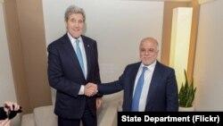 Menlu AS John Kerry berjabat tangan dengan Perdana Menteri Irak Haider al-Abadi sebelum pertemuan bilateral di sela-sela Forum Ekonomi Dunia di Davos, Swiss, 21 Januari 2016.