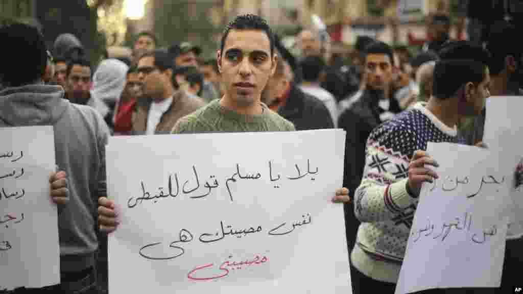 "An Egyptian man holds a poster with Arabic that reads ""Muslims and Copts are in the same tragedy"" during a protest against the slaying of Egyptian Coptic Christians in Libya by militants associated with the Islamic State group, in Cairo, Egypt, Feb. 16, 2"