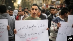 "FILE - An Egyptian man in Cairo holds a poster with Arabic that reads ""Muslims and Copts are in the same tragedy"" during a protest against the slaying of Egyptian Coptic Christians in Libya by militants associated with the Islamic State group."