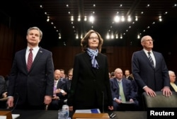 "FBI Director Christopher Wray; CIA Director Gina Haspel and Director of National Intelligence Dan Coats arrive with other U.S. intelligence community officials to testify before a Senate Intelligence Committee hearing on ""worldwide threats"" on Capitol Hill, Jan. 29, 2019."