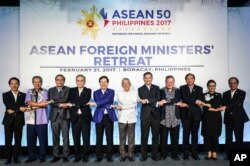 FILE - In this photo provided by Presidential Communications Operations Office ASEAN, foreign ministers from the Association of Southeast Asian Nations (ASEAN) link arms during the ASEAN Foreign Ministers' Retreat in Boracay, Aklan province, central Philippines, Feb. 21, 2017.