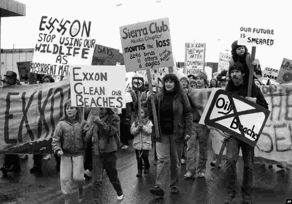 FILE - People in Kodiak carry signs to protest the Exxon oil spill in Anchorage, Alaska, May 27, 1989.