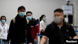 Para penumpang yang tiba dari Batam melewati pos pengukuran suhu di Singapore Cruise Center di tengah pandemi virus corona di Singapura, 5 Maret 2020. (Foto: Reuters)