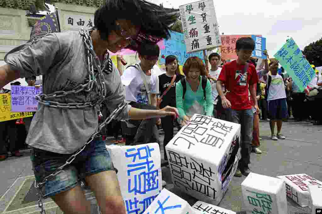 Students enact a skit demanding a freeze in tuition increases along side thousands of anti-government protesters demanding higher wages and better treatment during a May Day march in downtown Taipei, Taiwan, May 1, 2012. (AP Photo)