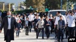 Anak-anak dari komunitas Yahudi ultra-Ortodoks Israel berjalan di luar sekolah Talmud Yahudi di kota Ashdod yang melanggar aturan lockdown, 22 Januari 2021. (Foto: JACK GUEZ / AFP)