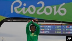 Silver medal Ethiopia's Feyisa Lilesa crosses his arms as he celebrates on the podium after the men's marathon at the 2016 Summer Olympics in Rio de Janeiro, Brazil, Aug. 21, 2016.