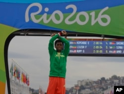 FILE - Silver medalist Feyisa Lilesa of Ethiopia crosses his writsts as he celebrates on the podium after the men's marathon at the 2016 Summer Olympics in Rio de Janeiro, Brazil, Aug. 21, 2016. He had made the same gesture of protest as he approached the finish line of the race.