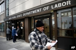 Visitors to the Department of Labor are turned away at the door by personnel due to closures over coronavirus concerns, Wednesday, March 18, 2020, in New York. Applications for jobless benefits are surging in some states